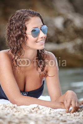 young happy woman in black bikini on beach