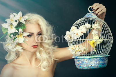 Blonde holding a cage with a bird