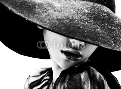 girl in black hat touching face and lips