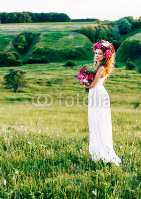 Girl with flowers in the hair in a wedding dress.