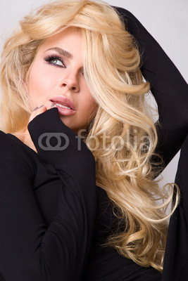 portrait of a beautiful woman on a white background and long curly blond hair and a sensual mouth with long lashes, wearing a black dress with long sleeves