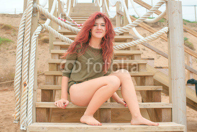 attractive redhead resting on the beach on a wooden staircase