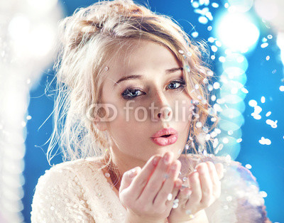 Blond lady blowing pieces of crystal