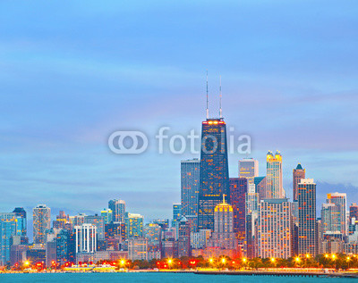 Chicago Illinois skyline at sunset with illuminated downtown buildings