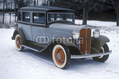 An antique car in the snow in New England