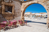 Stone arch in main square of Marzamemi and some chairs of a bar