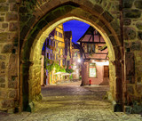 View of Riquewihr, Alsace, France, through city wall gate at nig