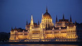 Illuminated Hungarian Parliament Building on bank of Danube river