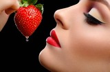 Girl eats strawberries on a black background