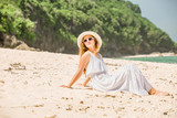 Young woman in long white dress and hat relaxing on tropical beach having great summer time. Vacation, lifestyle, travel, concept