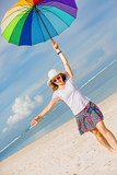 Cheerful young girl with rainbow umbrella having fun on the