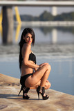 Beautiful girl in black bikini and high heels at Danube river