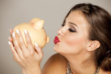 beautiful young woman with makeup posing with piggy bank