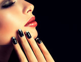 Beautiful model brunette shows black and silver French manicure on nails. Luxury fashion style, manicure nail , cosmetics and makeup .