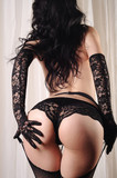 Sexy buttocks of a woman wearing fishnet stockings, suspenders, sexy panties and long lace gloves