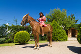 Beautiful young brunette with red dress riding brown-blond horse