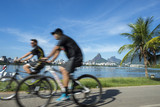 Athletic Brazilians cycling in motion blur at Lagoa Rodrigo de Freitas lagoon, Rio de Janeiro, Brazil