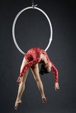 Beautiful aerialist doing acrobatic stunt on hoop