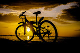 Silhouette of mountain bike with sunset sky at sea