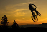 Mountain bike stunt against nice sunrise
