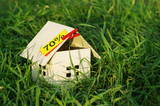 House from paper with an empty yellow card with an inscription of 70% in a green grass. Image of purchase or sale of the house. Discounts for real estate. Model of cardboard house.