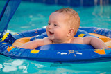 Happy infant playing in pool while sitting in baby float