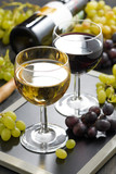 white and red wine in glasses, grapes in the background