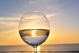 glass with white wine above sunset sea ocean