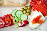 Spanish salad comprising of sliced chorizo, manchego cheese topped with quince jam, peppadew peppers stuffed with soft cheese accompanied by cucumber and tomato. Served on a wooden platter with bread.