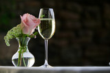 Pink rose with a glass of white wine.