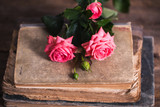 pink roses and books on the old wood