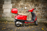 Red scooter on Paris streets standing against stone wall