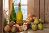 bottles and glass of cider with apples