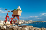 Old red bicycle along the seafront of Syracuse, Sicily