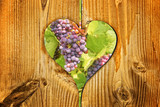 Red wine grapes in a wooden heart