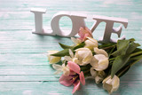 Fresh  white and pink tulips flowers and word love on wooden tur