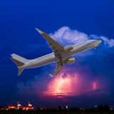Commercial airplane flying with clouds and thunderstorm backgrou