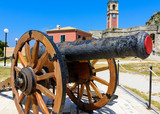 An ancient cannon with Clock Tower on background at the wall of Corfu Old Fortress, Greece.