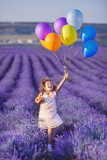 Smiling girl sniffing flowers in a lavender field