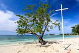 White cross on a beach with green tree.
