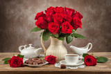 table with cups of tea, chocolates and a bouquet of roses