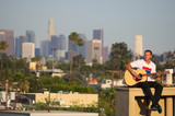 Guitar player on rooftop with Los Angeles skyline in background