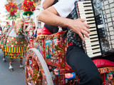 Accordion player wearing a folkloristic dress and playing on a characteristic sicilian cart
