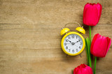 Clock nad tulips on wooden table.