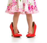 Kid girl in big mommy shoes isolated on white