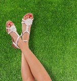 Slim female legs on grass